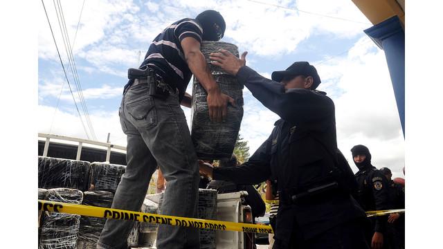 Honduras national policemen unload packages of cocaine.jpg_10739444.jpg