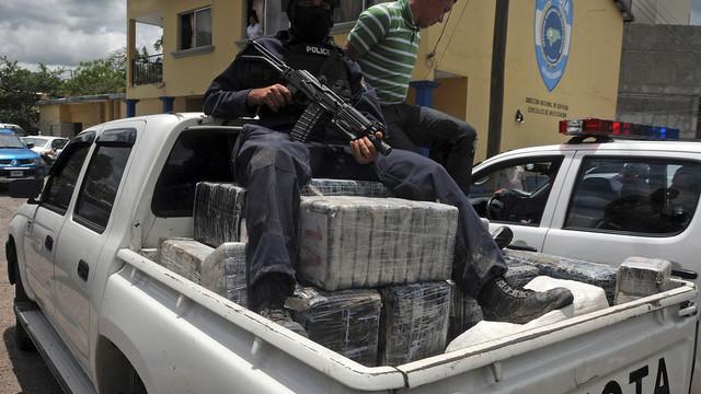 A Honduras national policeman sits on packages of cocaine that were brought to Tegucigalpa, Honduras.jpg_10739448.jpg