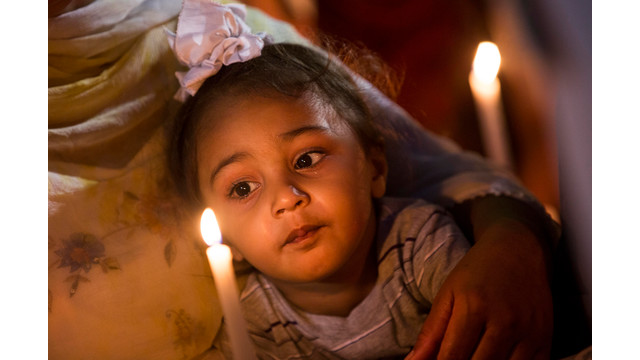 A child is held at a vigil in Oak Creek, Wisconsin.jpg_10757039.jpg