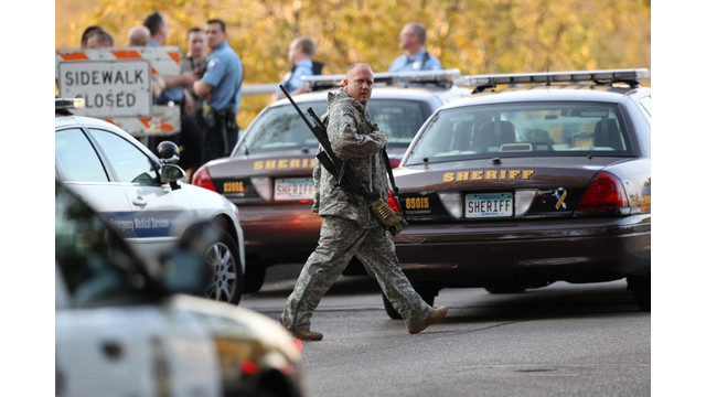 An officer walks through the area as police investigate a shooting.jpg_10795935.jpg