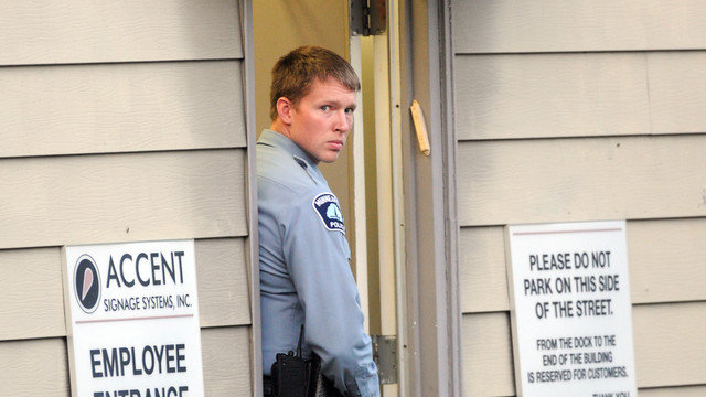A Minneapolis police officer stands at the entrance of Accent Signage Systems.jpg_10795938.jpg