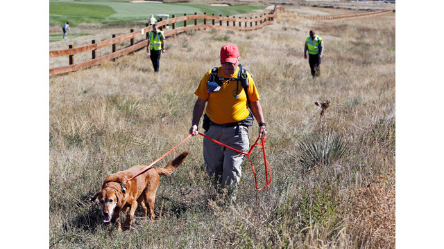 Denis McLaughlin leads his search and rescue dog through a field .jpg_10811214.jpg