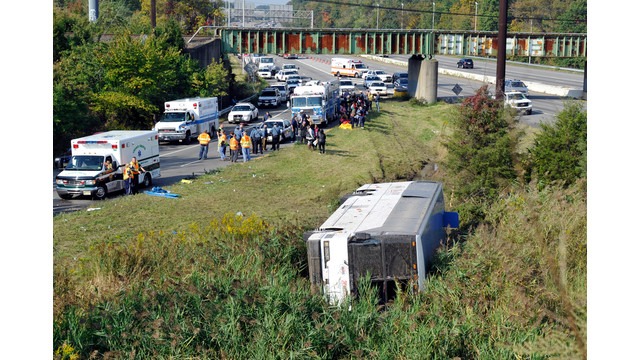 Rescue workers and passengers stand by after a bus overturned in a ditch at an exit ramp off Route 80 in Wayne, N.J..jpg_10809500.jpg