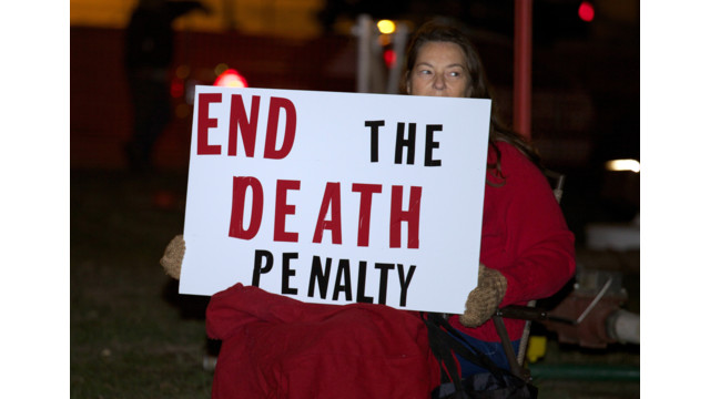 Death-penalty opponent Elaine Engelgau holds a sign during a protest .jpg_10814794.jpg
