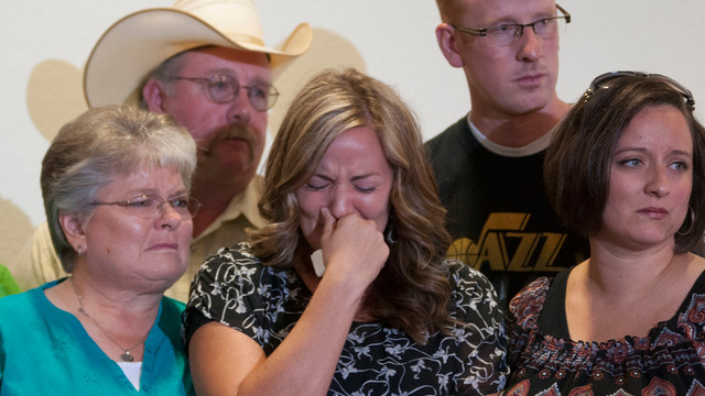 Christy Ivie, center, wife of Nicolas Ivie, holds back tears as she is surrounded by her family.jpg_10809497.jpg