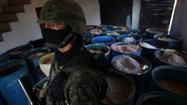 a soldier stands in a room full of barrels containing white and yellow powder.jpg_10813526.jpg